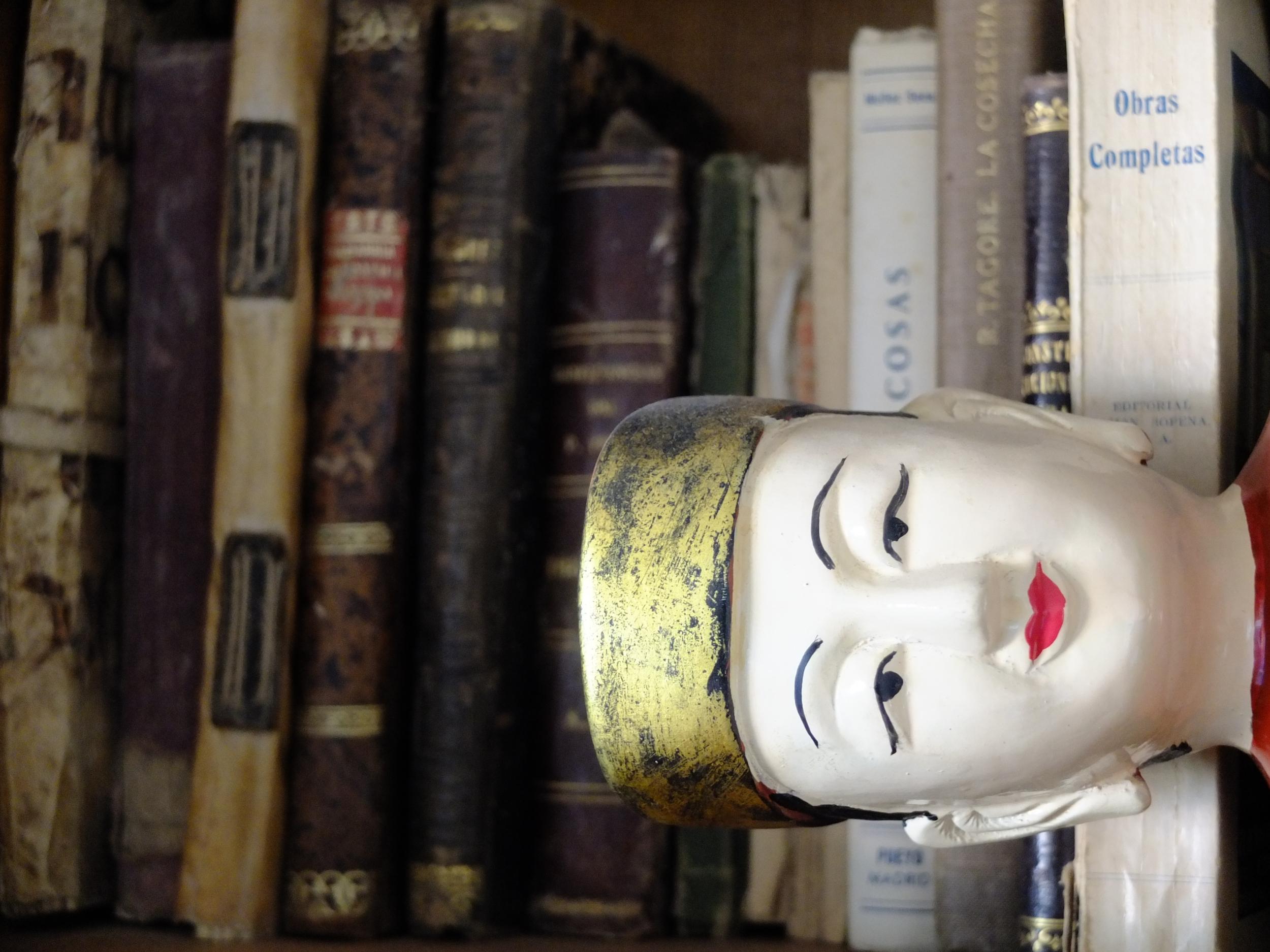 Buda tendido ante libros antiguos
